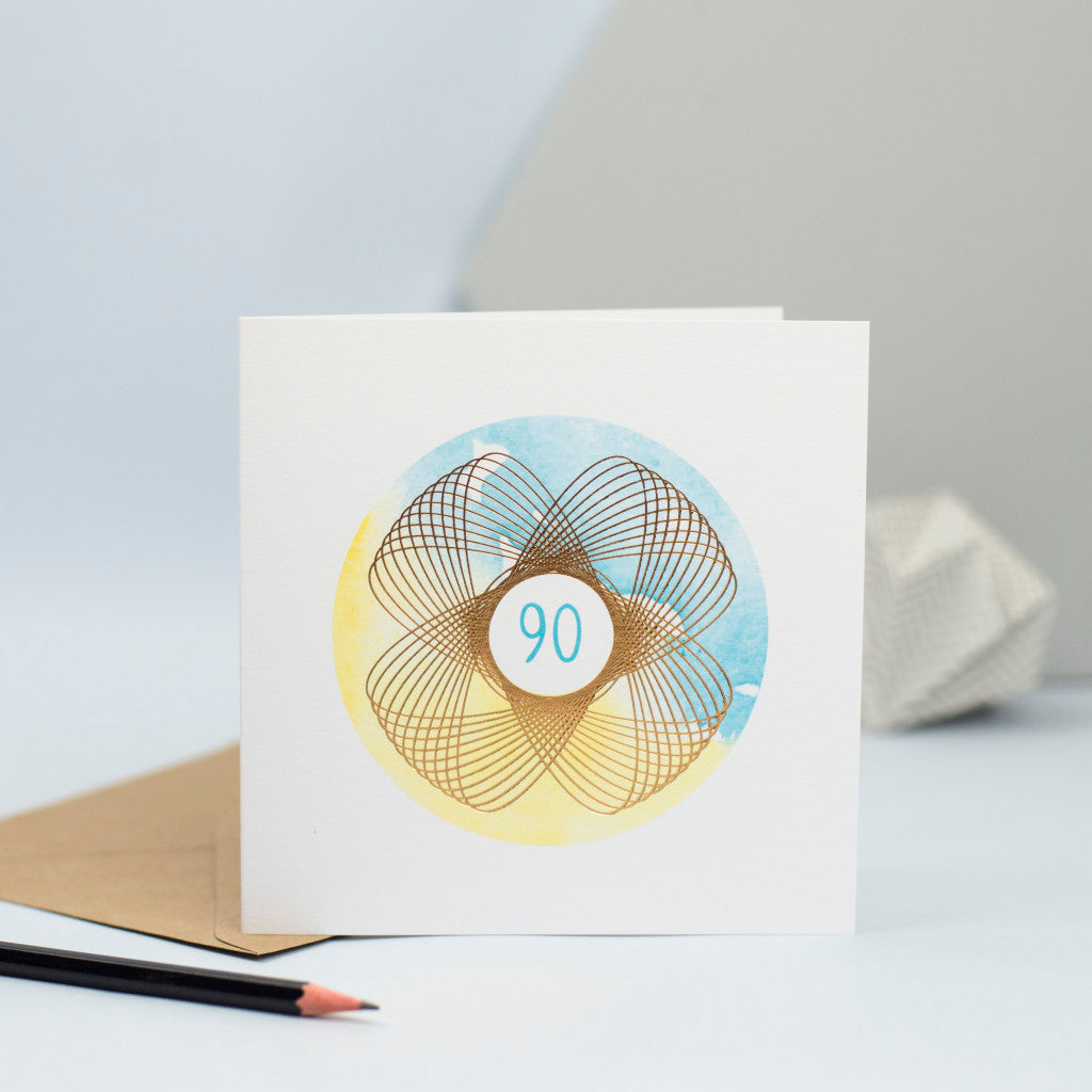 a unisex 90th birthday card with blue and yellow watercolour and a gold foil spirograph
