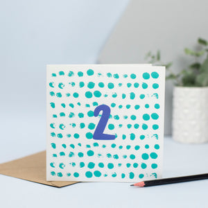A simple design created through mark making with green circular spots in the background and a blue 2 in the foreground. A gorgeous original unisex design for a 2nd birthday.