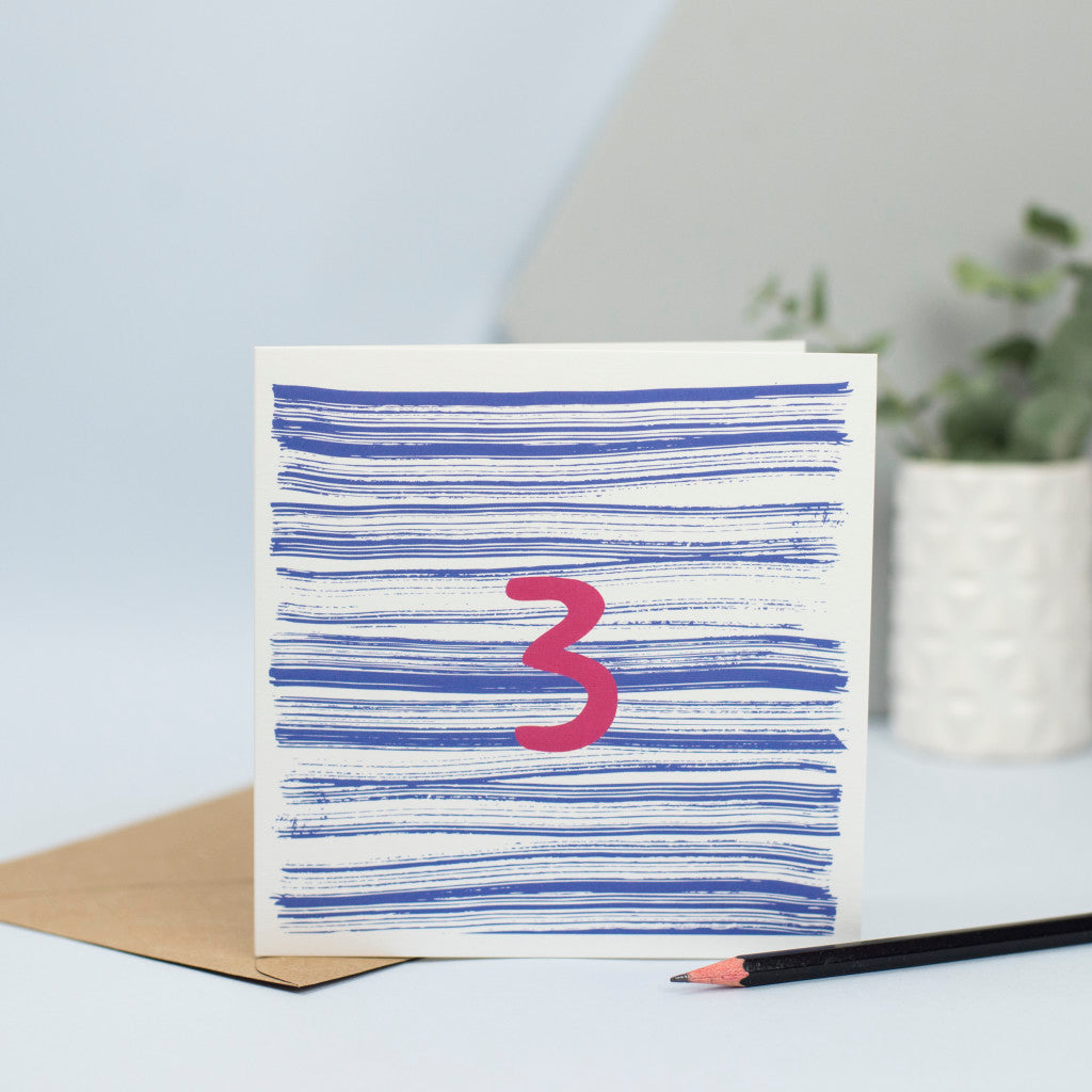 A unisex 3rd birthday card created through mark making with lines of textured blue in the background and a maroon number 3 in the foreground.