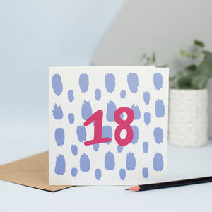 A simple design for an 18th birthday with large pale blue splurges in the background and the number 18 in maroon in the foreground.