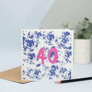 A 40th design created through mark making, with a blue textured background and a pink 40 in the foreground.