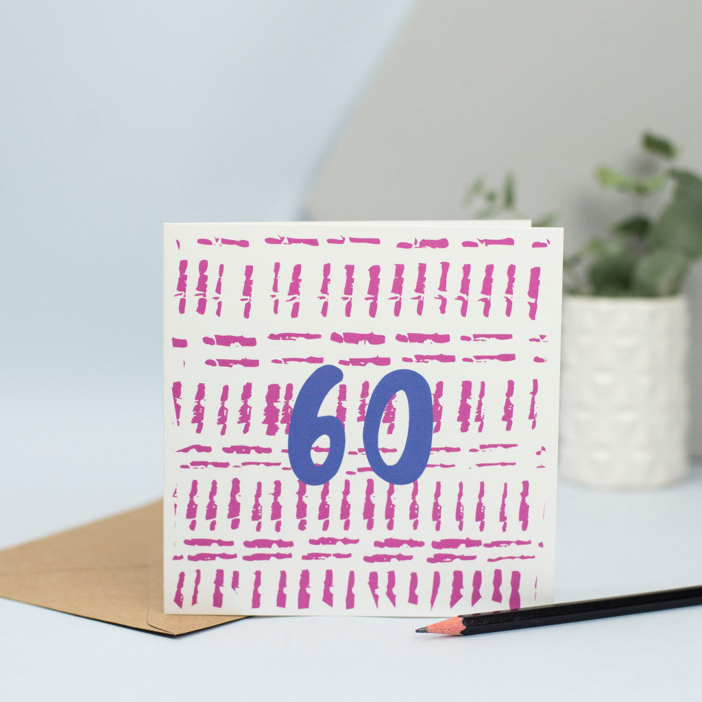 A 60th design created through mark making, with small maroon stokes in the background and a blue 60 in the foreground.