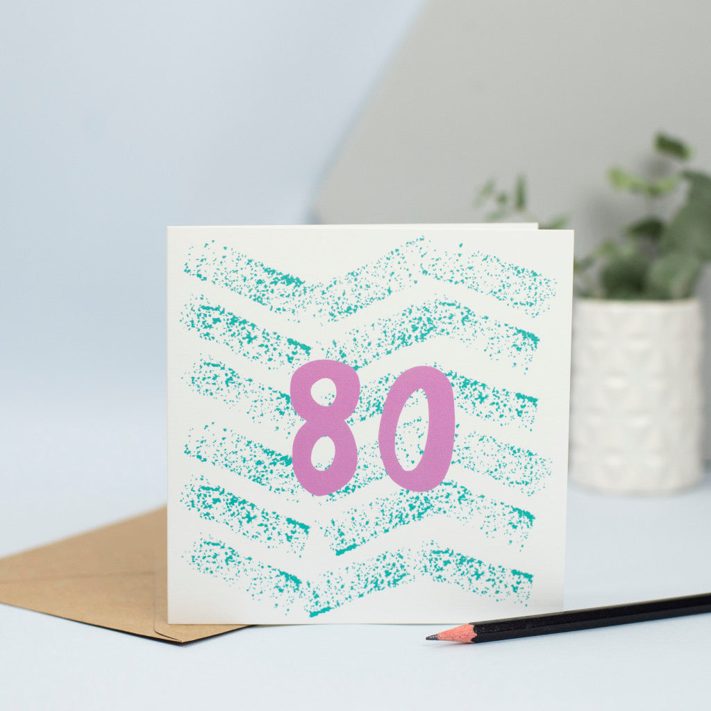 An 80th design created through mark making, with a green textured zig zags in the background and a pink 80 in the foreground.