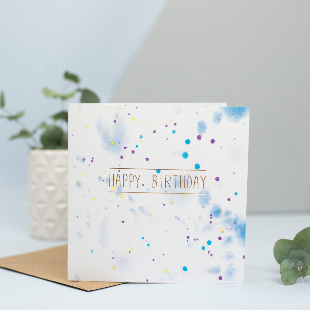 A watercolour splattered background with gold foiled Happy birthday on top