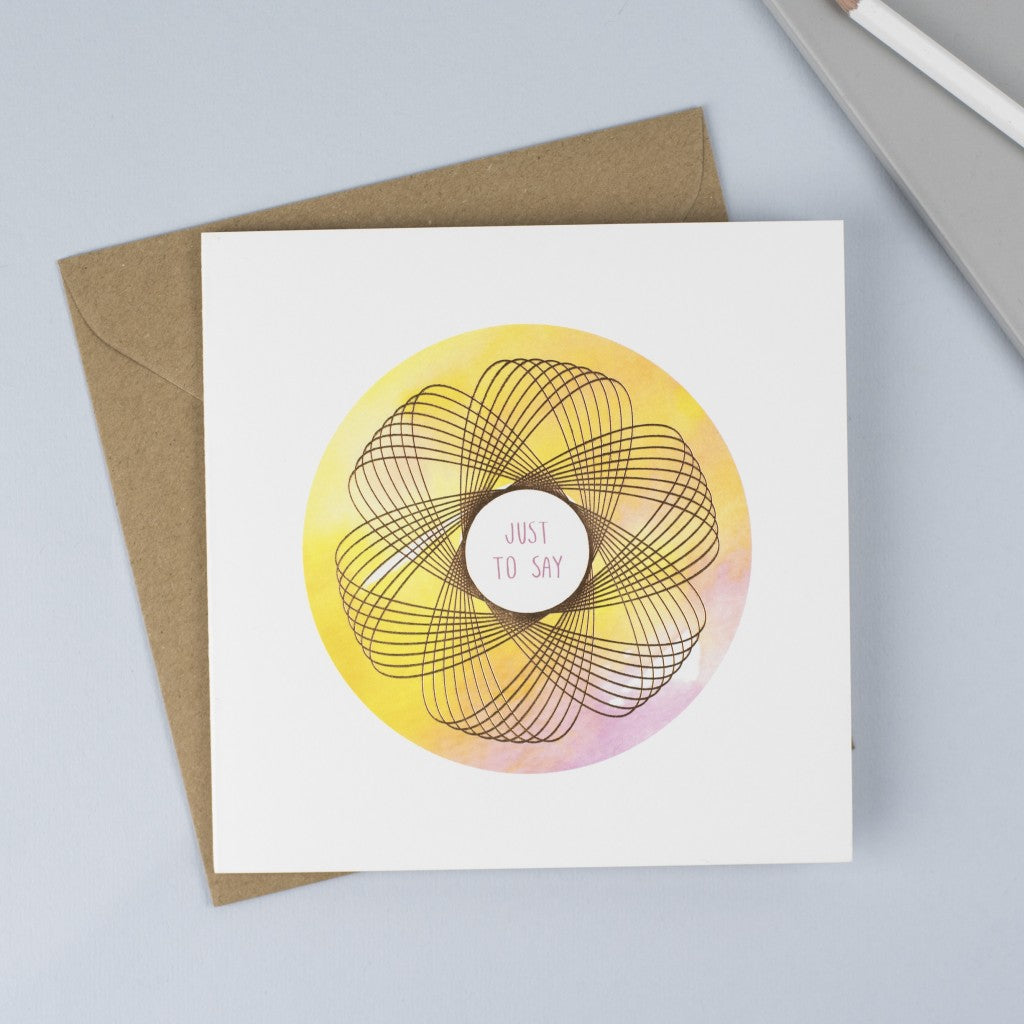 Copper foiled Spirograph with a pink & yellow watercolour background and a pink hand drawn font.
