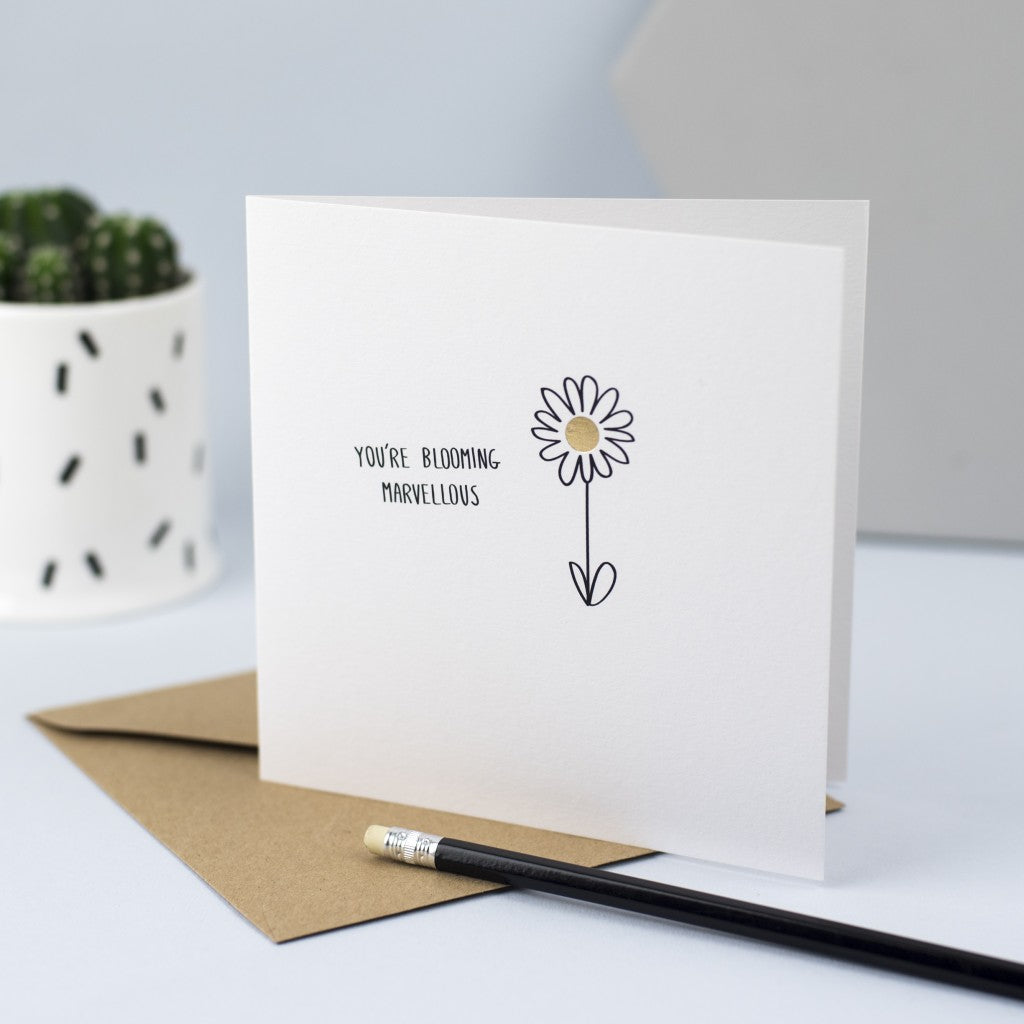 "Hand drawn illustration of a flower with gold foil and the words ""You're blooming marvellous""."