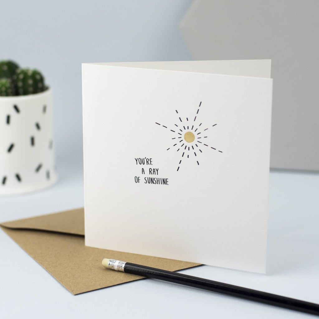 "Hand drawn illustration of a sun with gold foil and the words ""You're a ray of sunshine"""