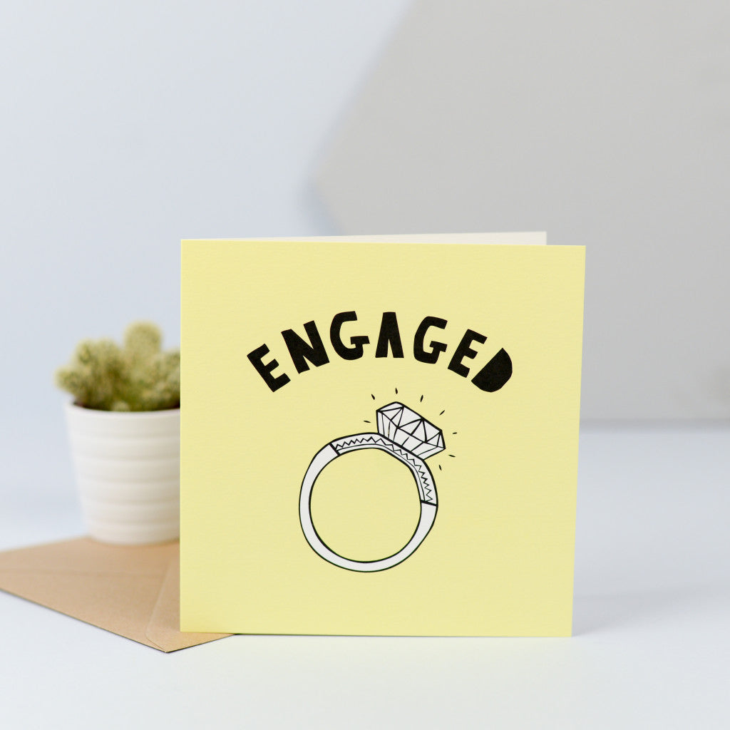 An engagement card with an illustration of a large diamond ring.