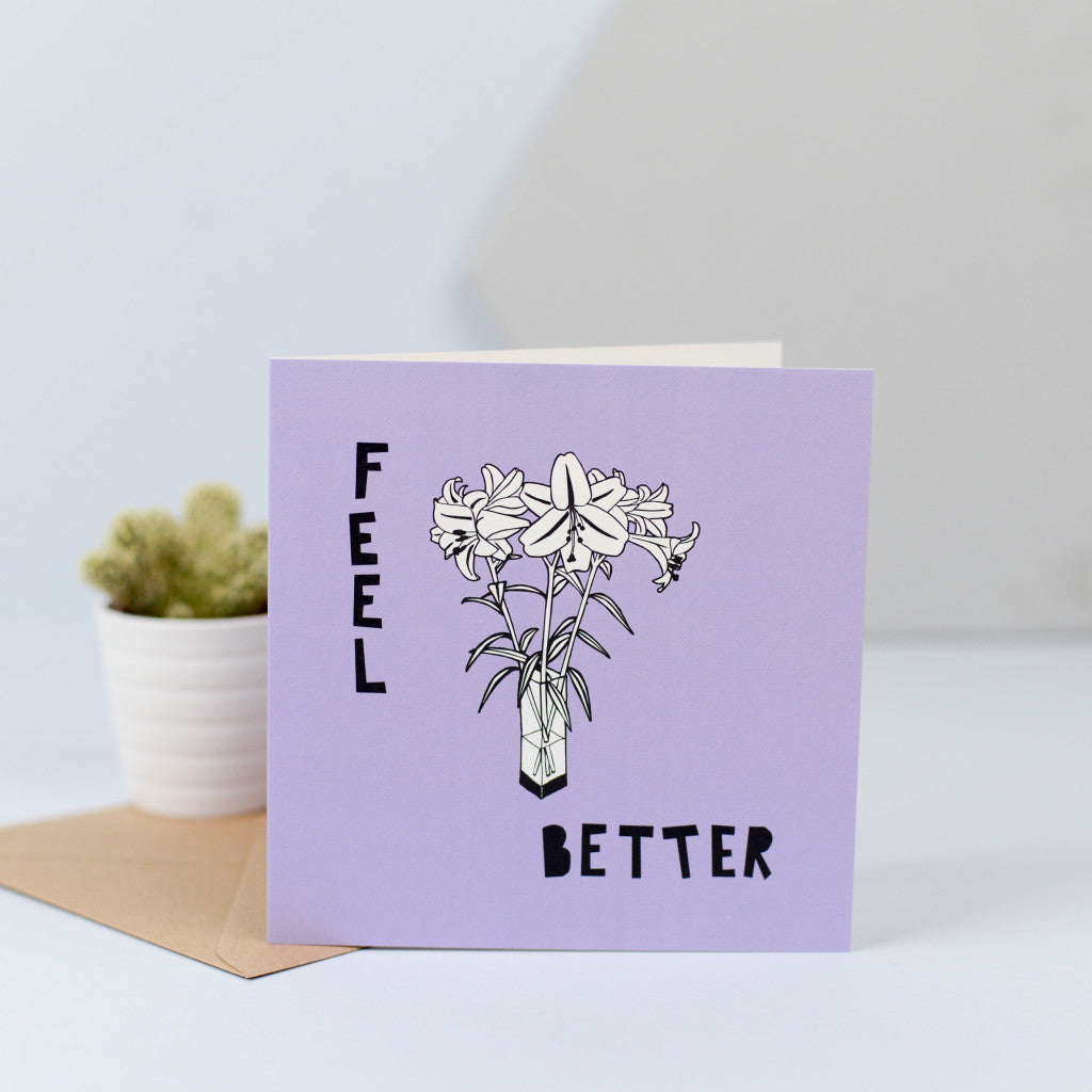 A card with some flowers and the words 'feel better'.