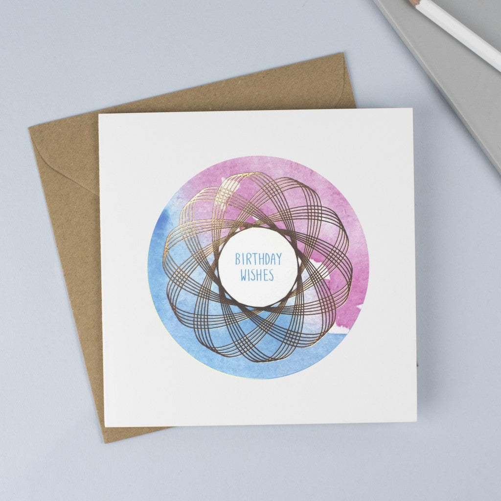 Copper foiled Spirograph with a pink & blue watercolour background and hand drawn font with the words Birthday Wishes in blue.