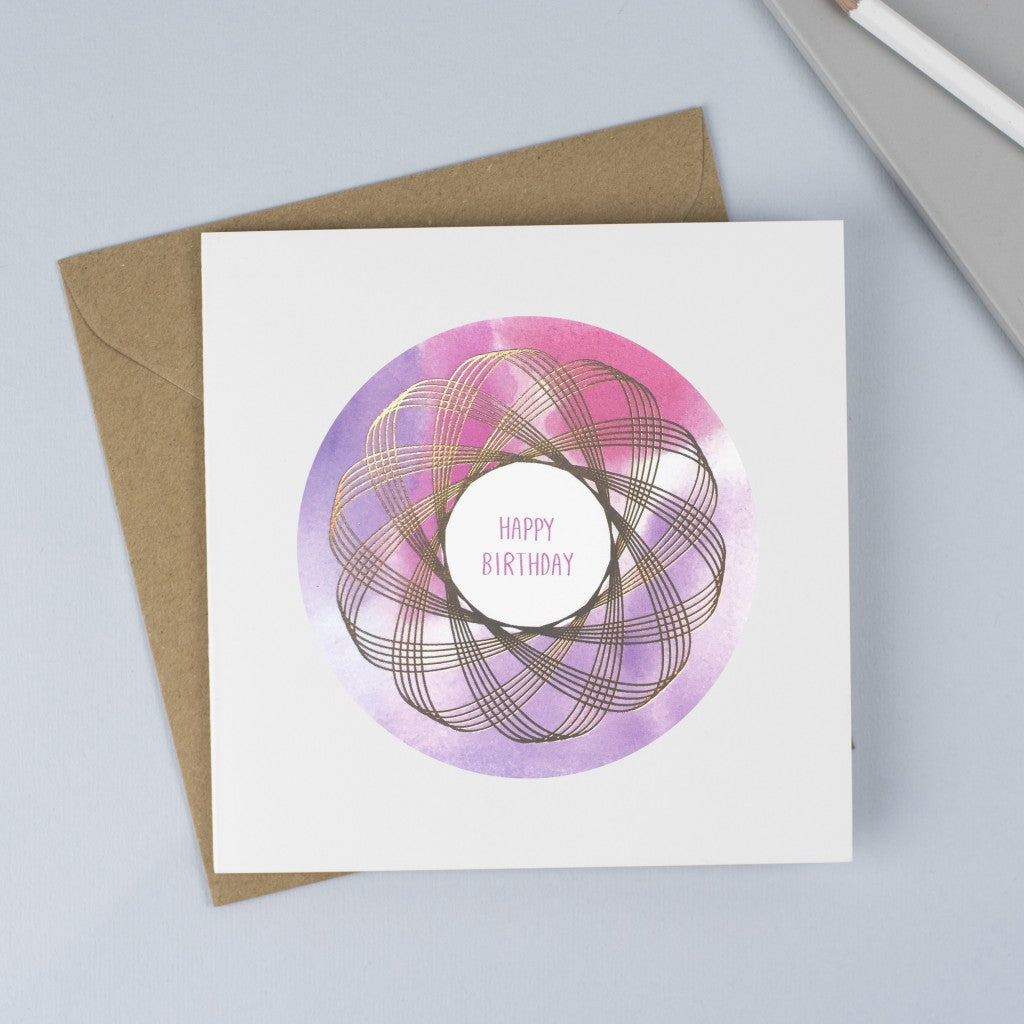 Copper foiled Spirograph with a pink and purple watercolour background and hand drawn font