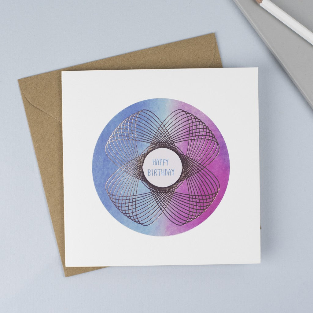 A beautiful foiled Spirograph with a blue and pink watercolour background and a hand drawn font.