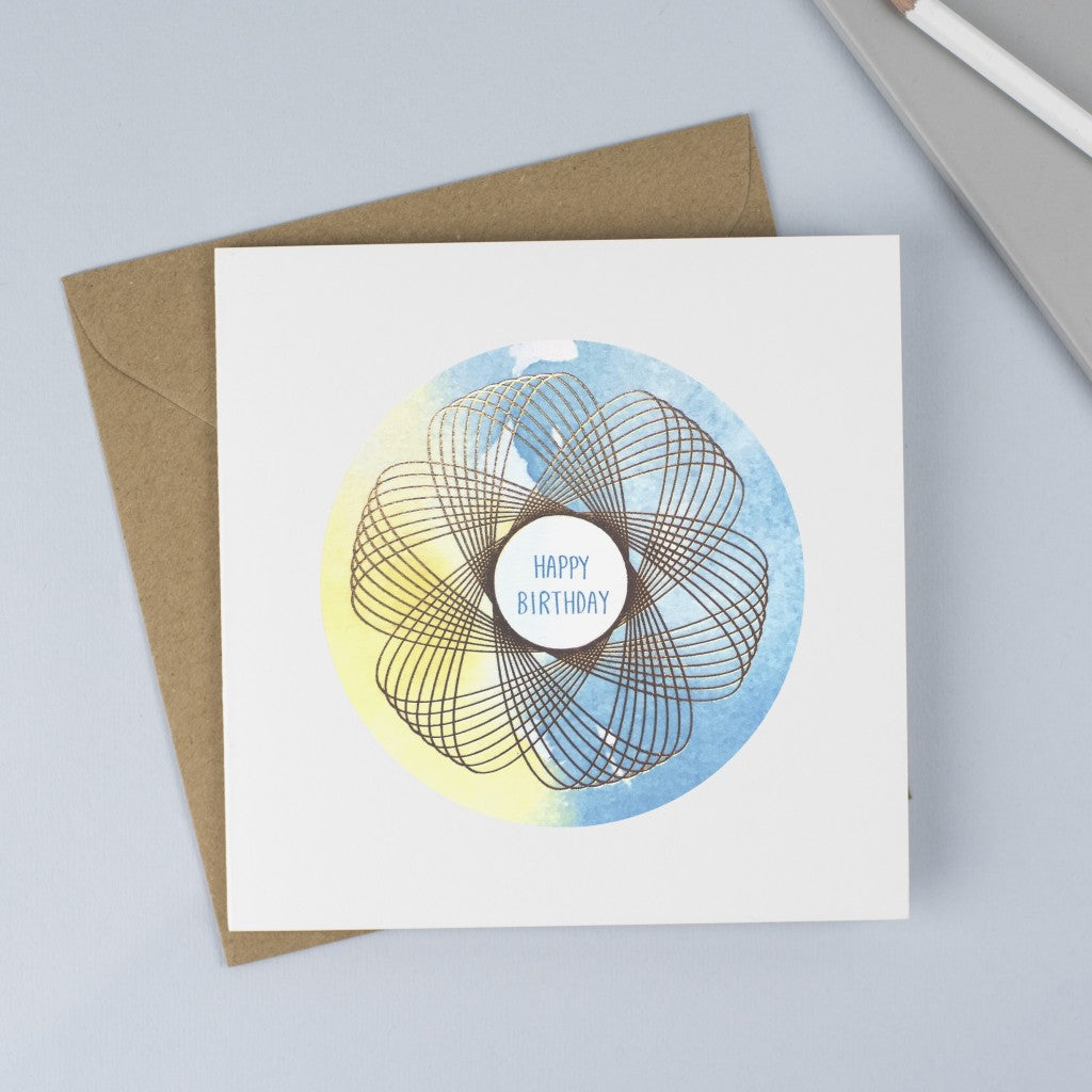 A unisex birthday card with a blue and yellow watercolour background and a gold spirograph on top.