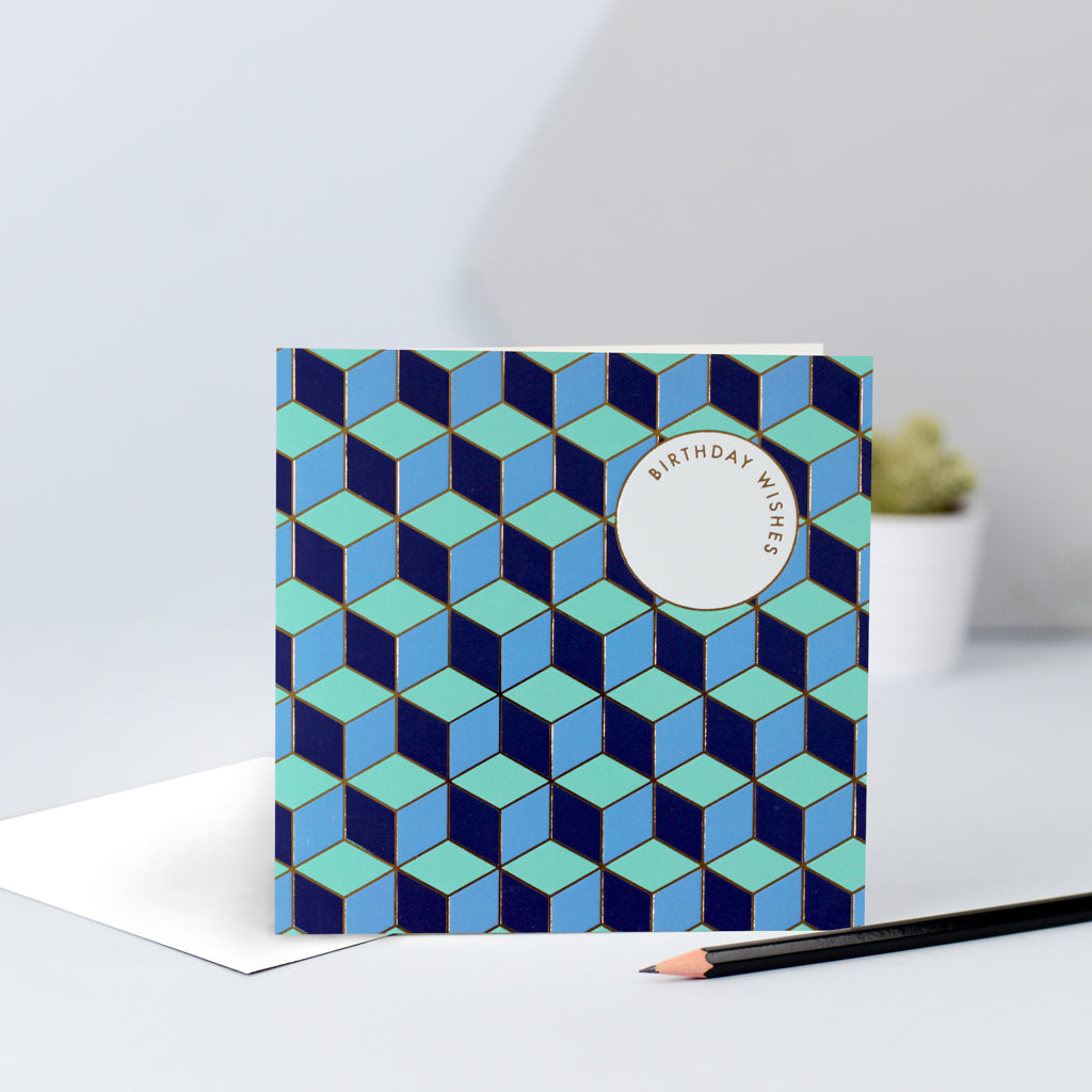 "A bold tessellating pattern with blues and greens, finished with gold foil and the words ""Birthday Wishes""."