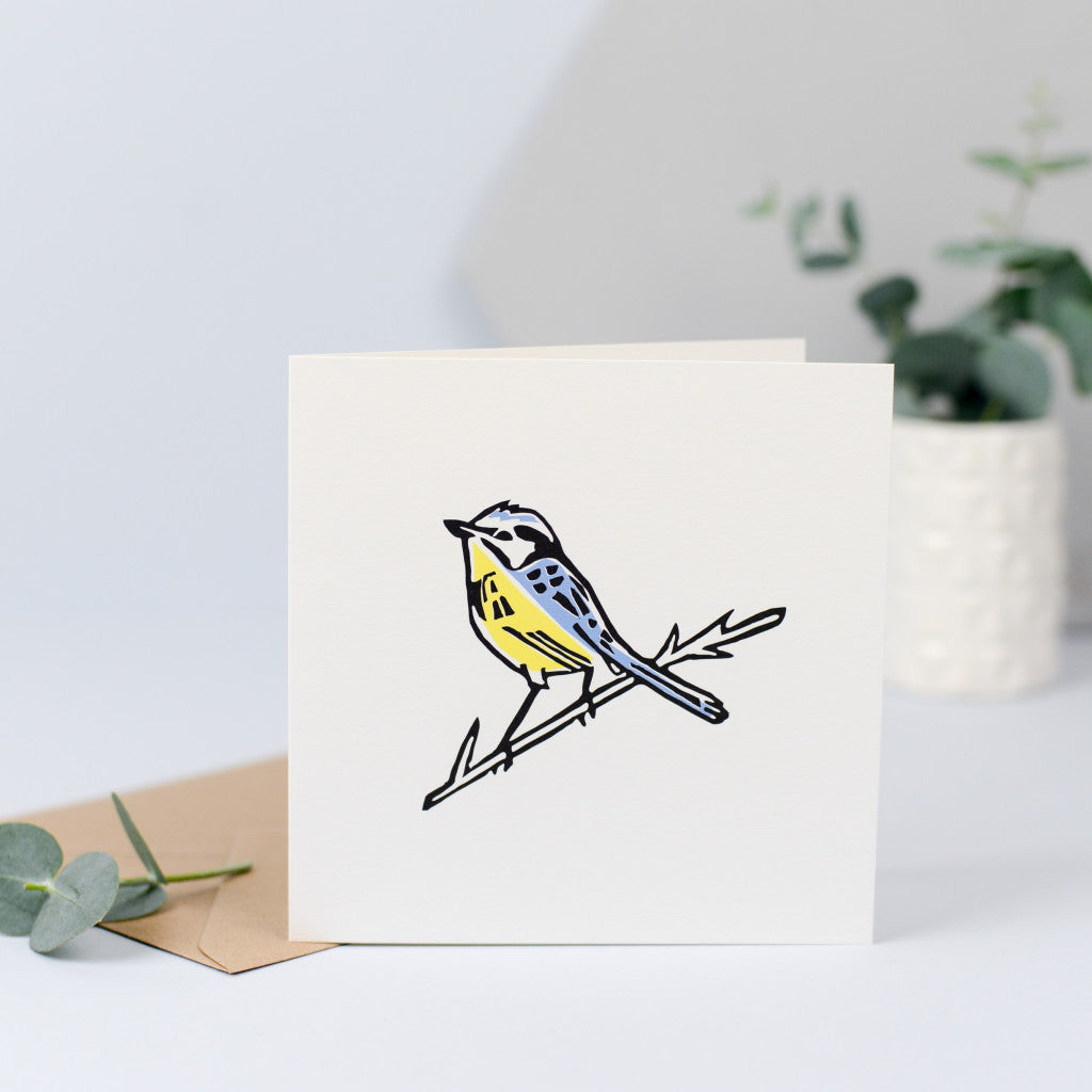 A beautiful illustration of a blue tit, originally hand carved in rubber and hand printed with a yellow breast and blue feathers and head.