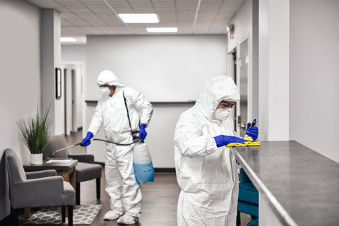 two people dressed in protective clothing disinfecting an office space to help prevent the spread of COVID-19