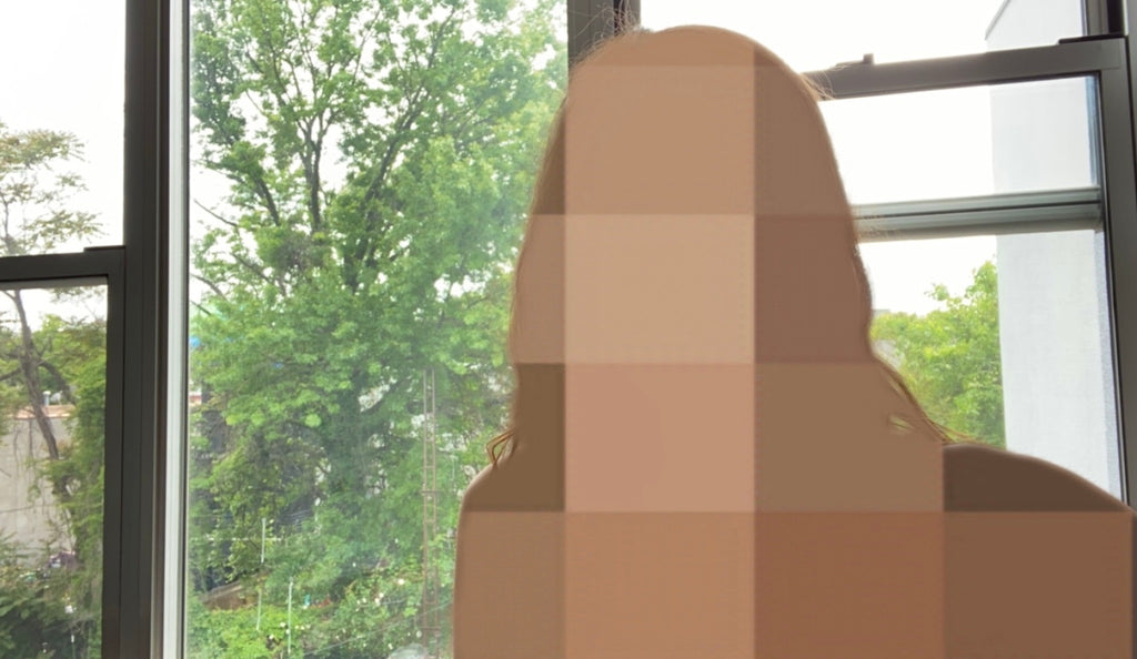 A photo taken with the Body Blur Instagram filter. The image is a selfie in front of a window, but the person is blurred with pixelated squares.