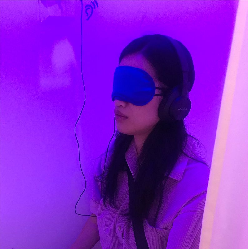 A viewer sits in one of the makeshift sound booths, surrounded by soothing blue and pink lighting. They have on a blindfold and headphones to listen to the CHKRA album.
