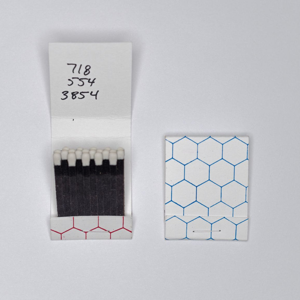 "An open matchbook lays flat next to a closed one on a white surface. The open one reads ""718-554-3854"" on the top, written in black marker."