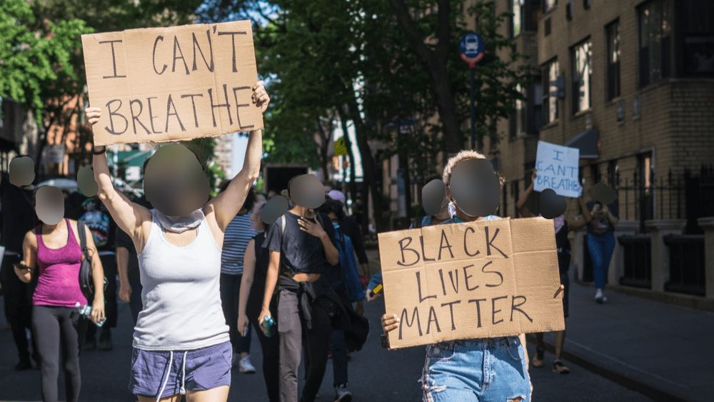 Black Lives Matter protest in the street with signs as dark ovals blur their faces.