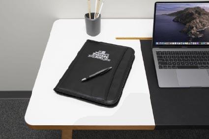 notepad with embroidered logo on a desk