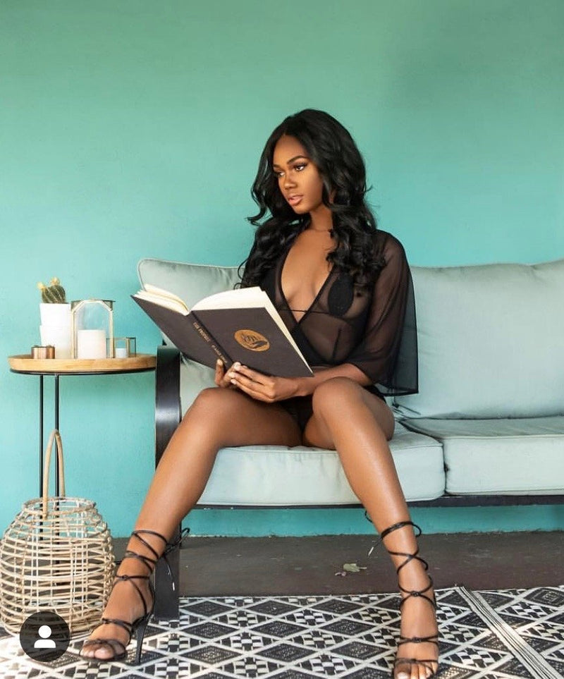 beautiful black girl reading in black lingerie set from Damita Belle for pools resorts