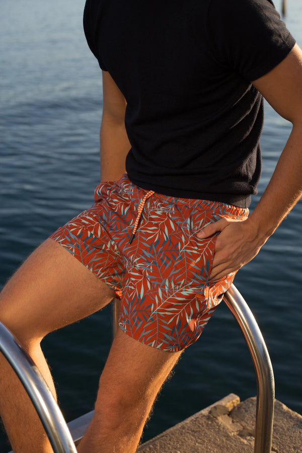 Man standing by water in Copper Bottom Swim orange swim trunks