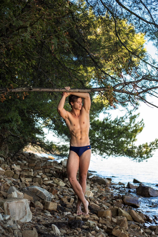 Man modelling navy blue speedo by the sea - Copper Bottom Swim