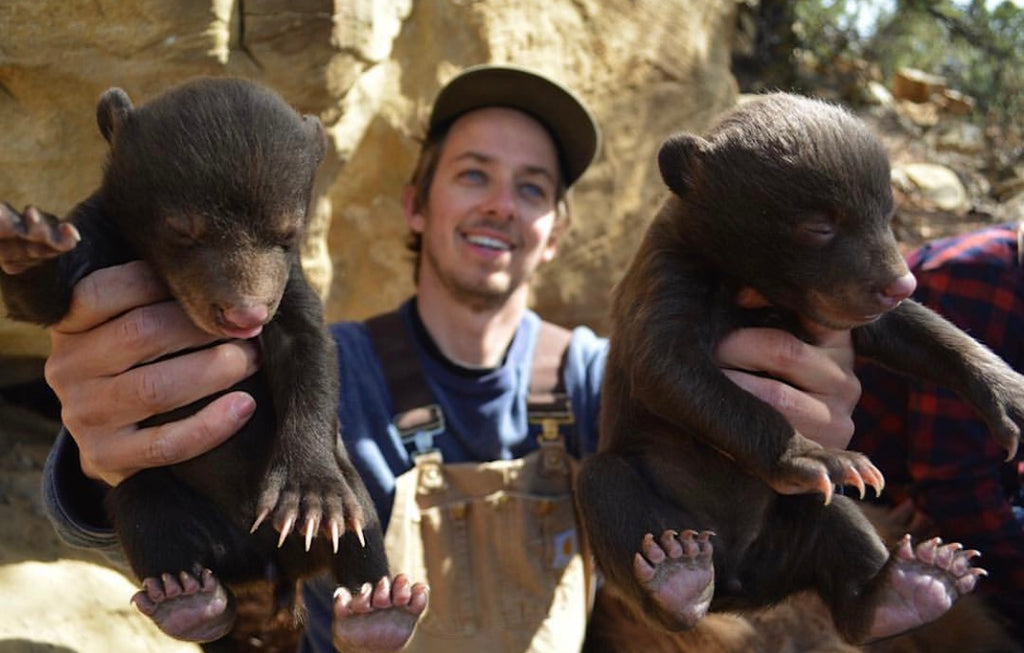 @grizkid wearing hat and overalls holding two black bear cubs