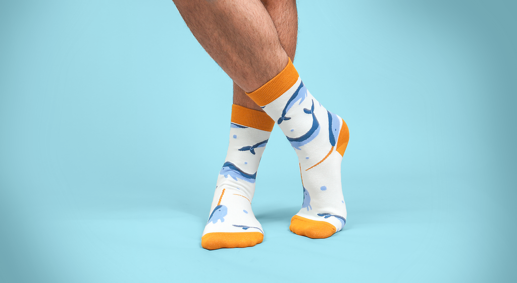 blue narwhal with orange accents at toe/heel pattern socks