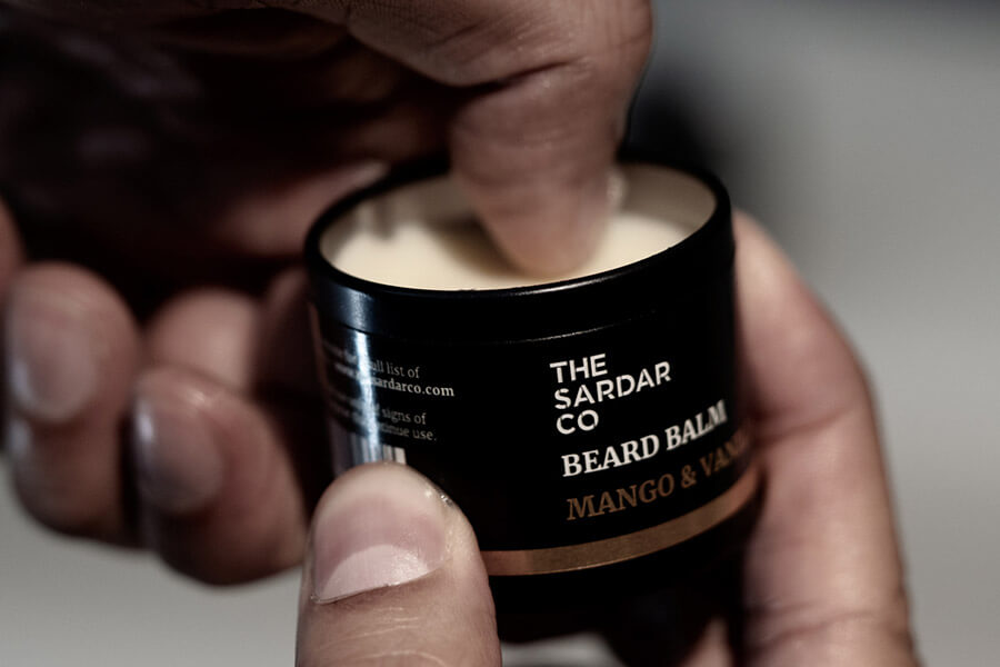 scooping beard balm out of tin