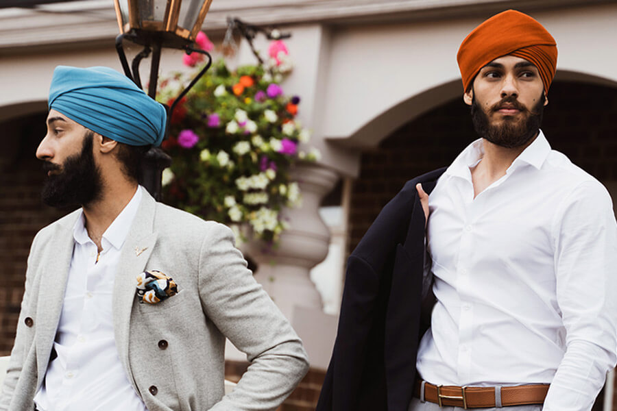 two sikh men wearing turbans in formal attire