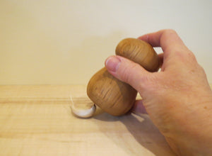 mashing garlic with hand made wooden garlic crusher