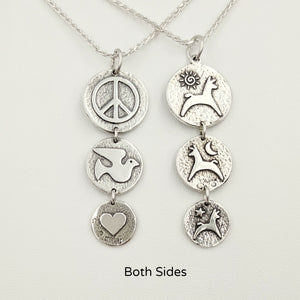 Both sides of the Alpaca or Llama Reversible Tri-Coin Drop Pendant - one side with pronking animals and sun, moon and star accents - the reverse side has a peace sign, dove and a heart - Sterling Silver