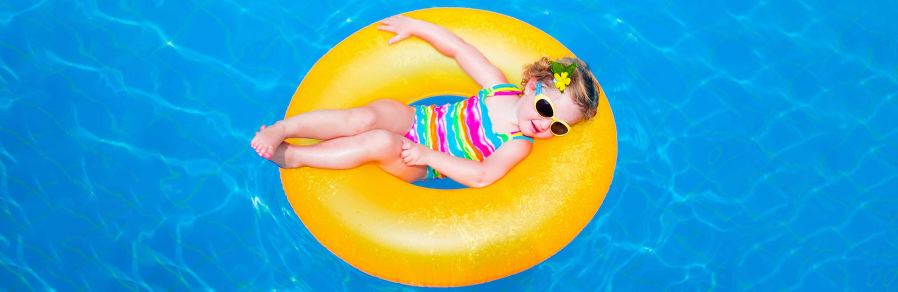 Little Girl in a yellow ring float in a swimming pool