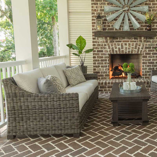 Woven outdoor sofa on a covered patio next to a fire place