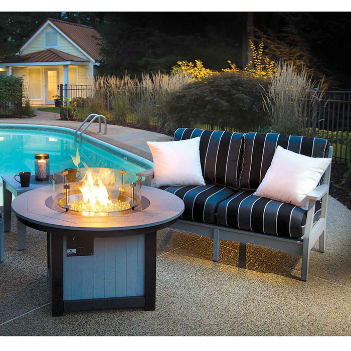 Grey Poly Lumber Love Seat with blue and black stripes by a swimming pool and fireplace