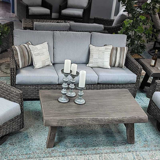 Woven outdoor sofa with blue cushions and striped pillows