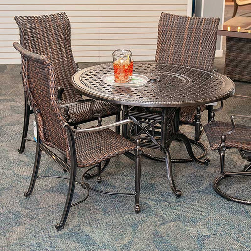 Round aluminum patio dining set surrounded by 4 woven patio dining chairs