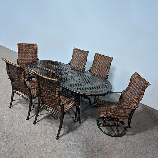 "86"" Oval outdoor dining table surrounded by 6 woven dining chairs"