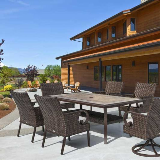 xbrown wicker dining set sitting on a concrete outdoor patio