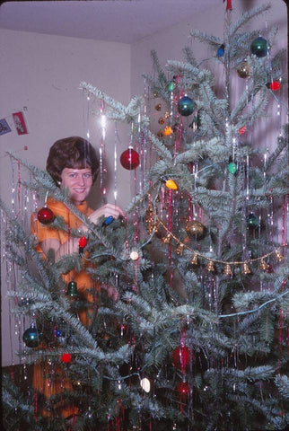 Woman hiding behind vintage Christmas tree