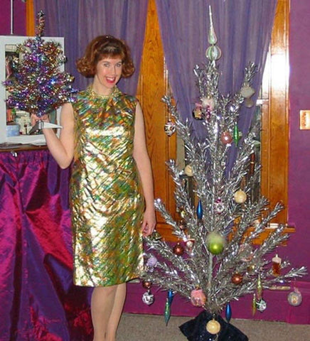 Woman in gold dress with vintage Christmas tree
