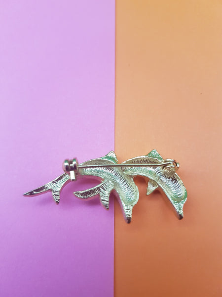 rear of two gold dolphins brooch