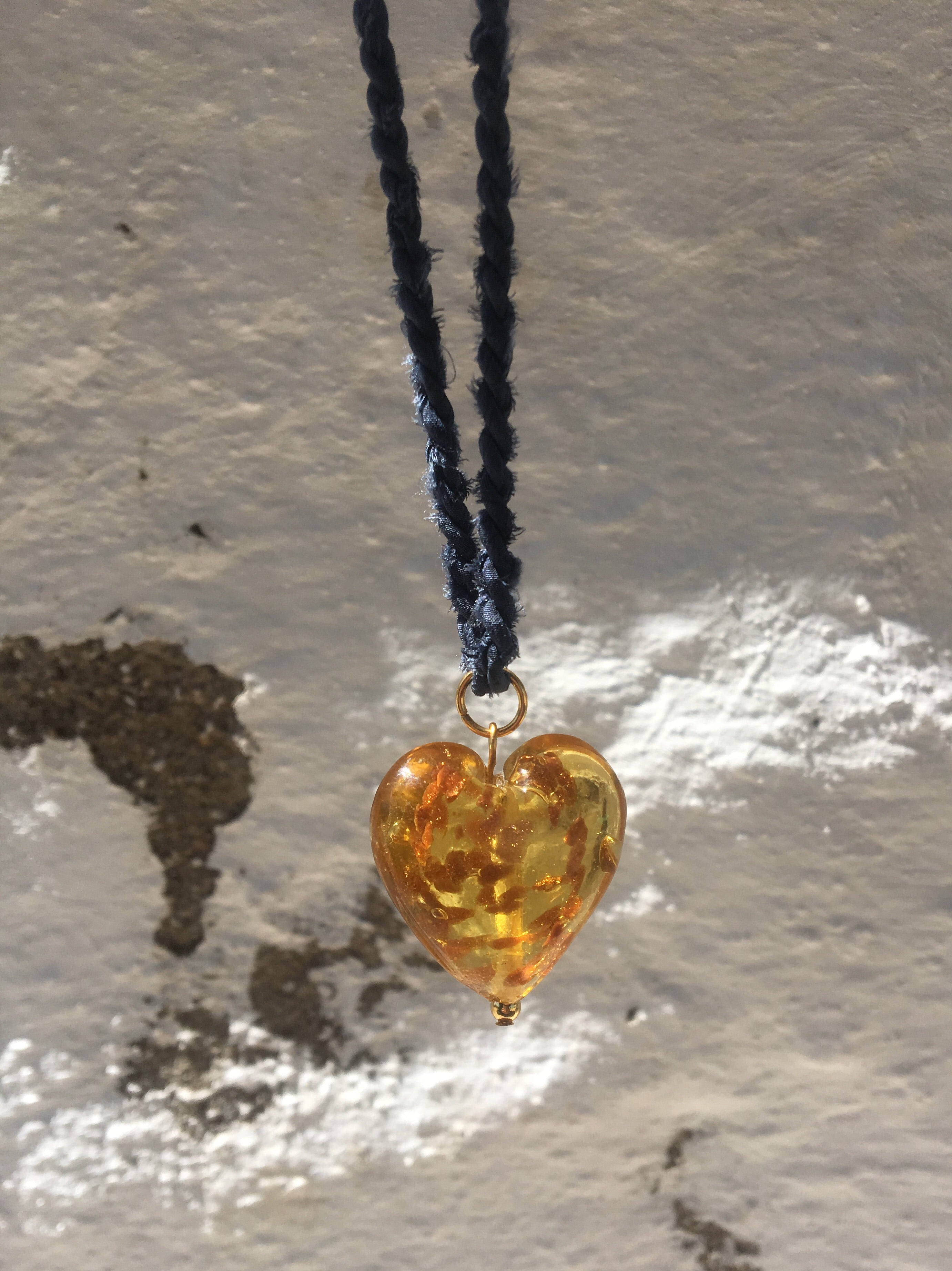 Handmade necklace with silk cord in navy and heart shaped Murano glass pendant in amber. Made to order and limited edition