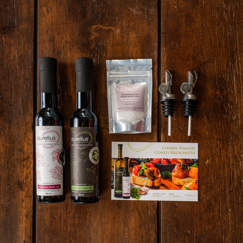 Image features one bottle of flavoured balsamic vinegar, one bottle of flavoured olive oil, a small bag of salt, two premium pour spouts, and recipe card for Cherry Tomato Confit Bruschetta.