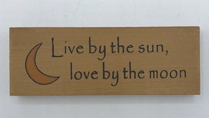 """Live by the sun love by the moon"" sign"