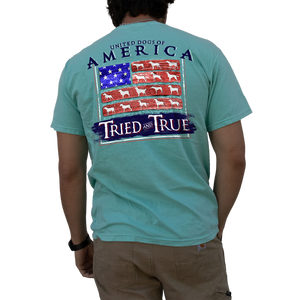 "Printed on a Comfort Color chalky mint colored t-shirt the united dogs of America design is a wooden version of the United States flag. With the red strips would be, are pieces of wood with white silhouttes of different species of hunting dog. ""United Dogs of America"" is in big letter above the design."