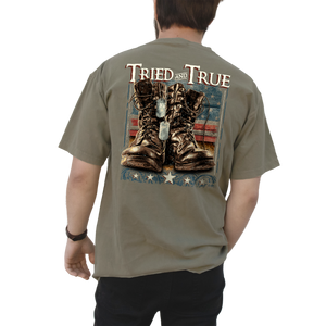 "Printed on a Comfort Color khaki colored t-shirt the military boots design, is a life like printed pair of brown military boots, with dog tags hanging off of one of them and the American Flag in the background. At the top ""Tried & True"" and at the bottom, stars."