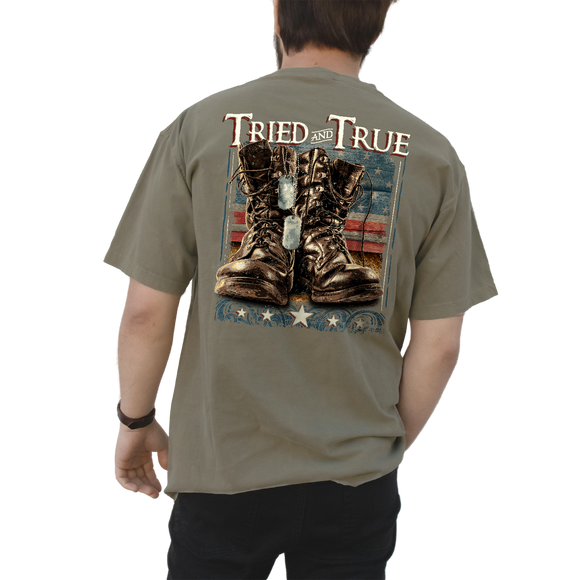 Printed on a Comfort Color khaki colored t-shirt the military boots design, is a life like printed pair of brown military boots, with dog tags hanging off of one of them and the American Flag in the background. At the top